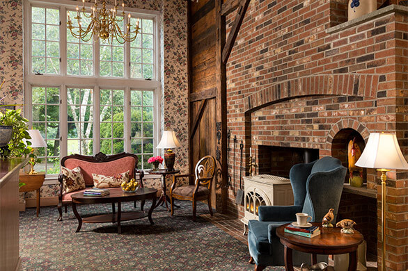 Period furniture and stove sit in a cozy vintage brick room