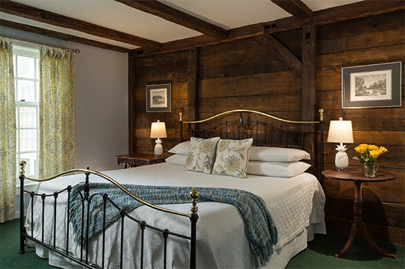 Chesterfield Inn room with comfortable, large bed and vintage wooden furnishings
