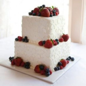 A stacked wedding cake with fruit on top