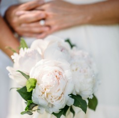 A wedding bouquet of white flowers being held in front of a white dress