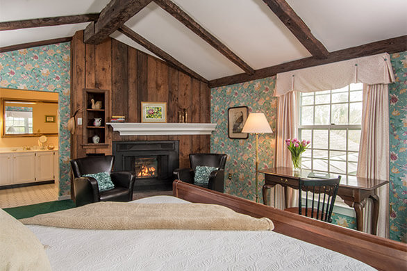 A soft bed in a cozy room with a fireplace in the corner