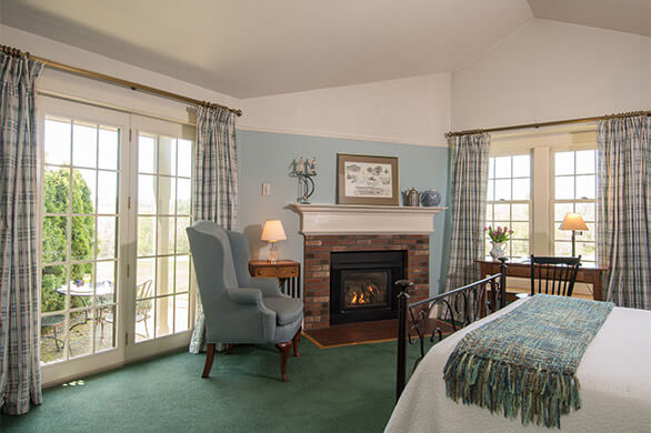 A bed, sitting area, and door to private porch near fireplace in the Chesterfield Inn's Room 23