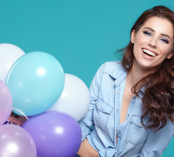 A woman holds balloons and laughs