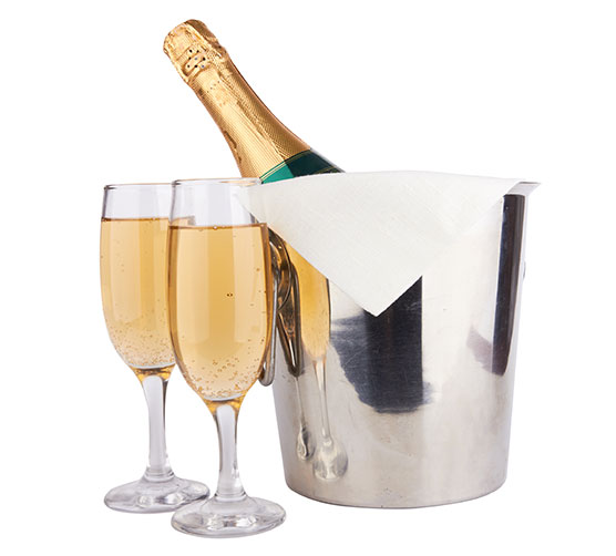 Two champagne glasses by a bottle of champagne in an ice bucket