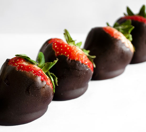 A close-up line of four chocolate covered strawberries