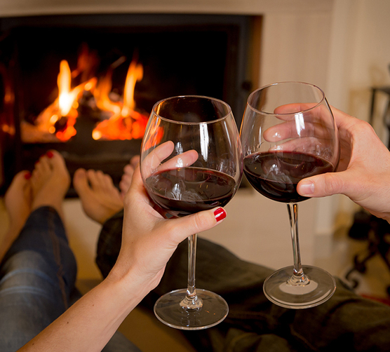 A couple toast wine while warming their feet in front of a fire