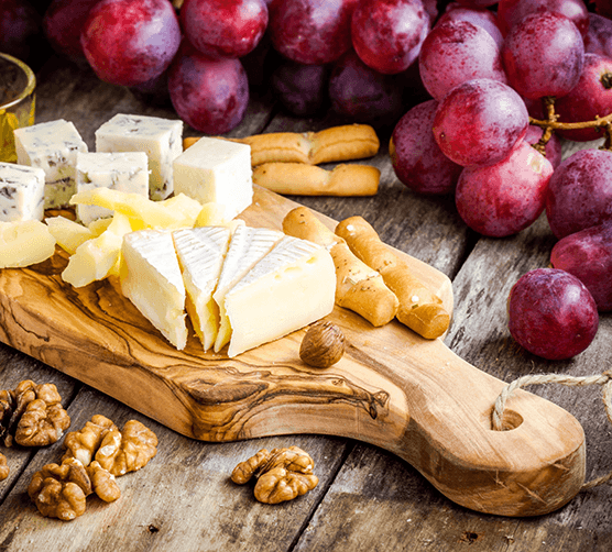 A tray of cheeses with grapes nearby