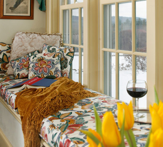 A bay window seat with a blanket, book, and wine glass in it.