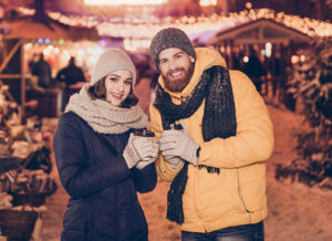 Couple outdoors in warm clothing with coffee cups