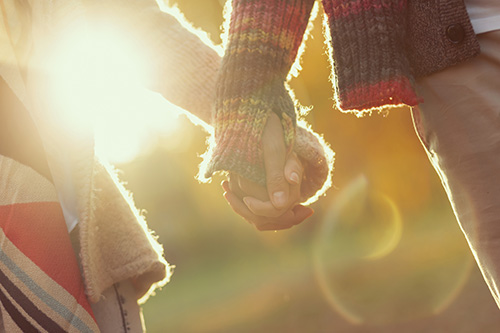 couple holding hands in the autumn light