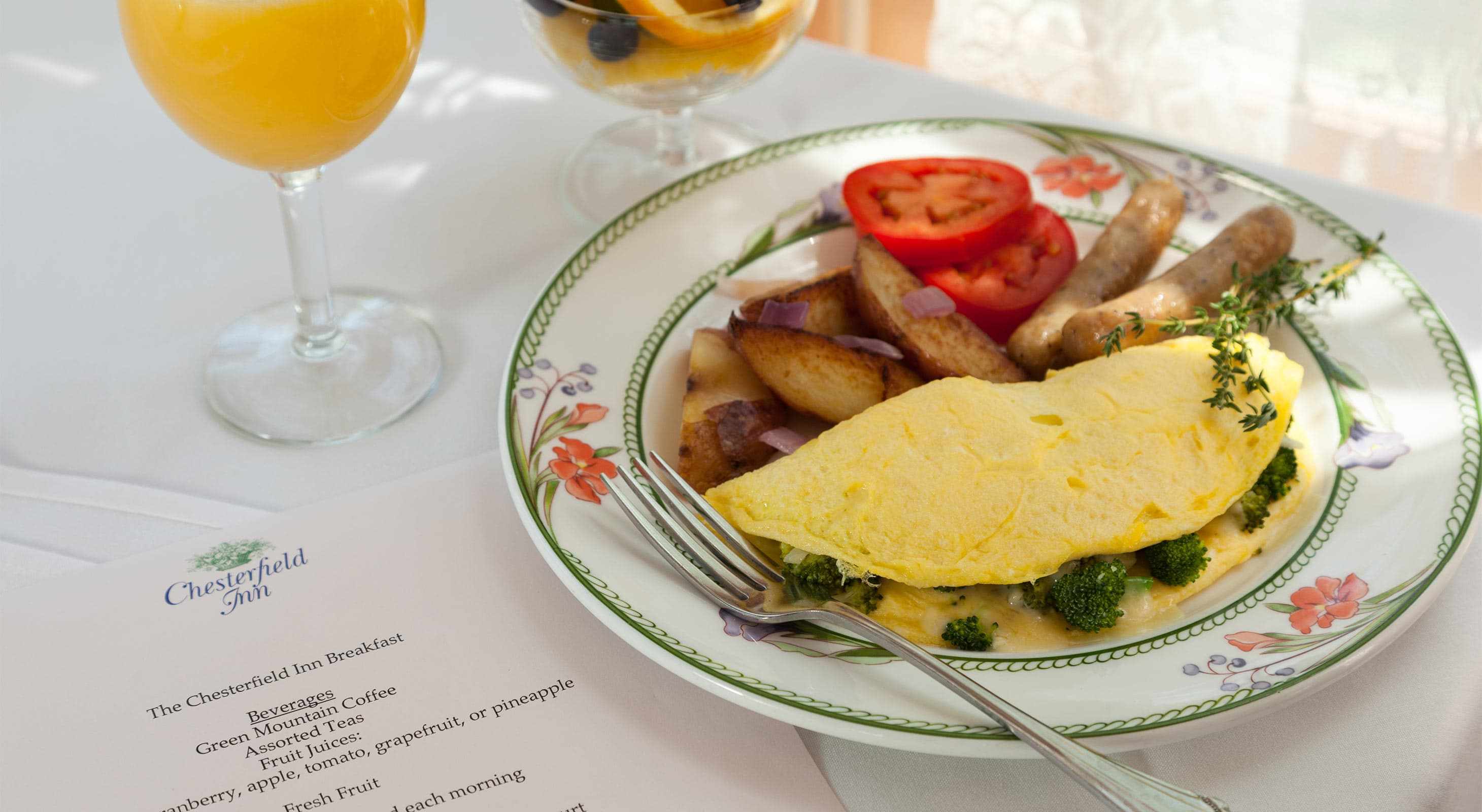 Breakfast Quiche with potatoes, orange juice and fruit in background