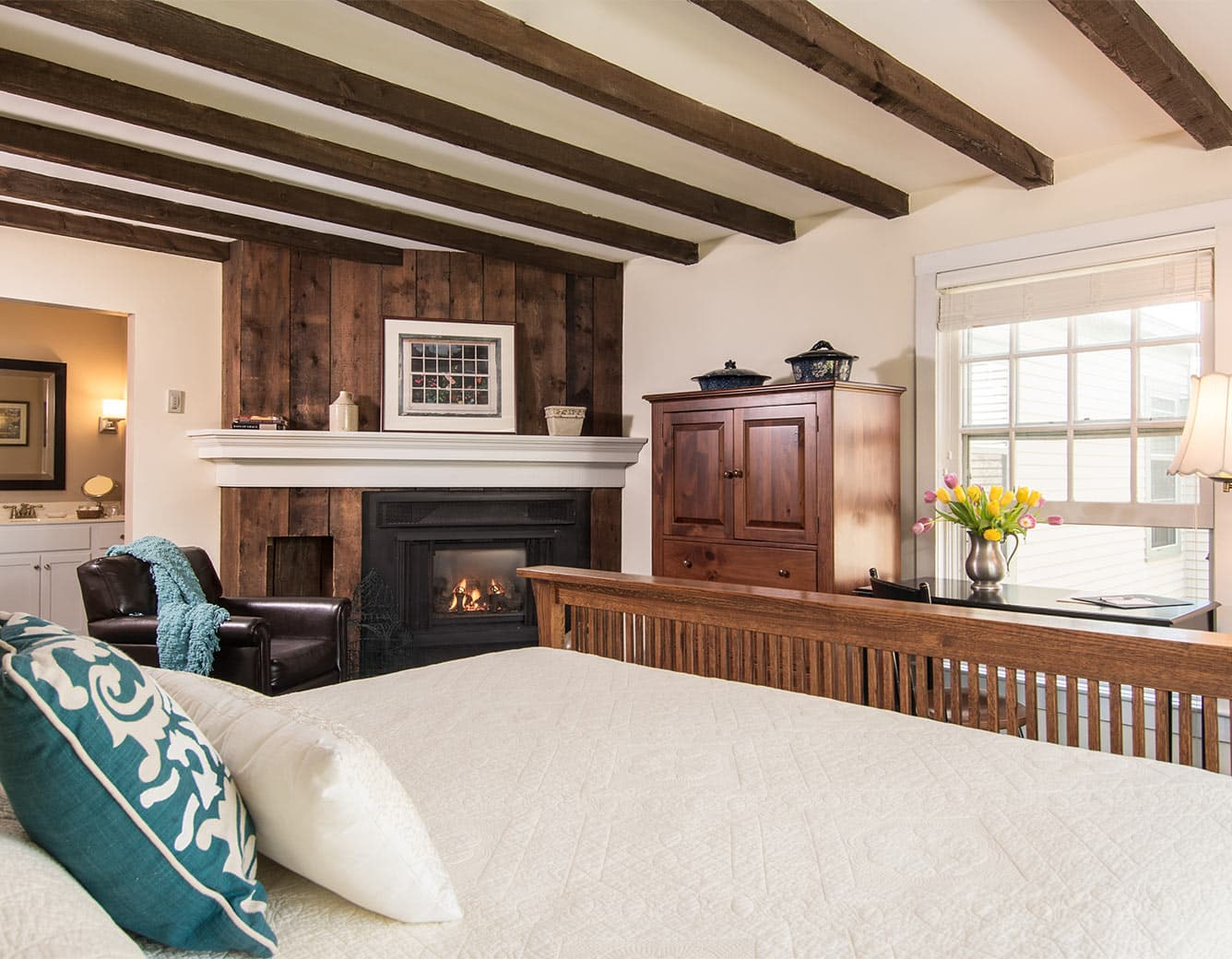 Soft bed with fireplace in background