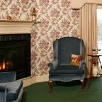 Fireplace with two plush chairs in winter