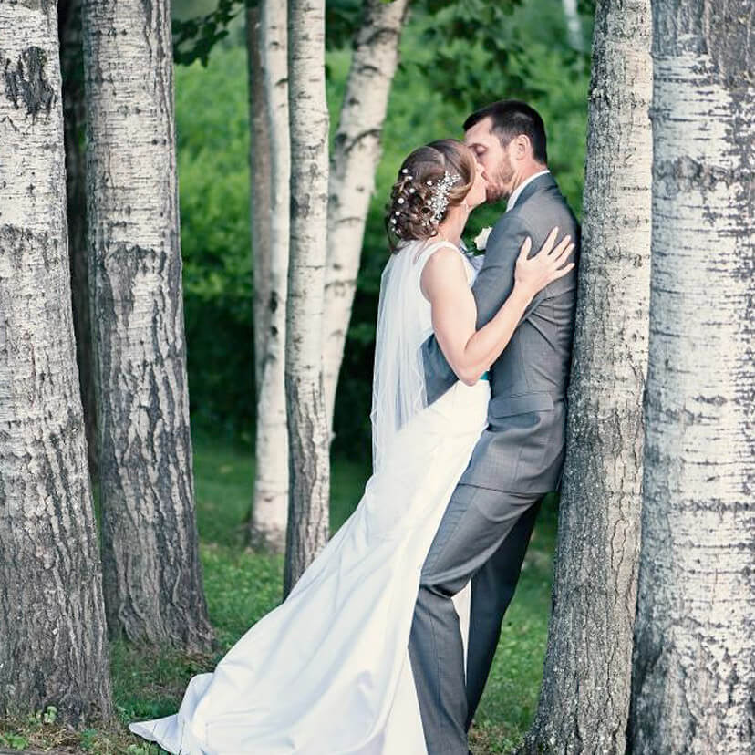 Wedding couple kissing in the trees