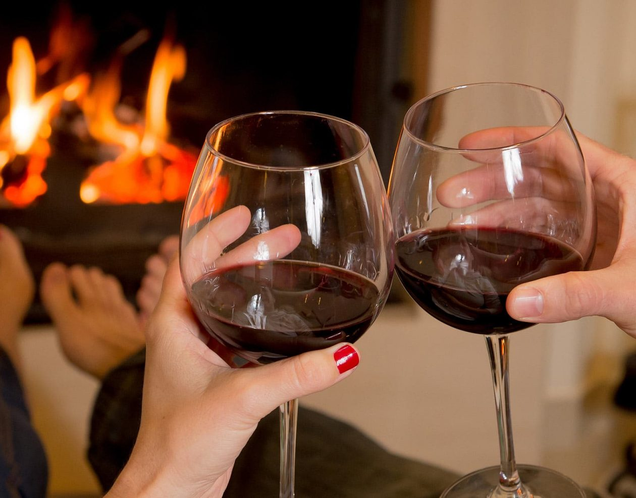 Toasting Red Wine in front of fireplace