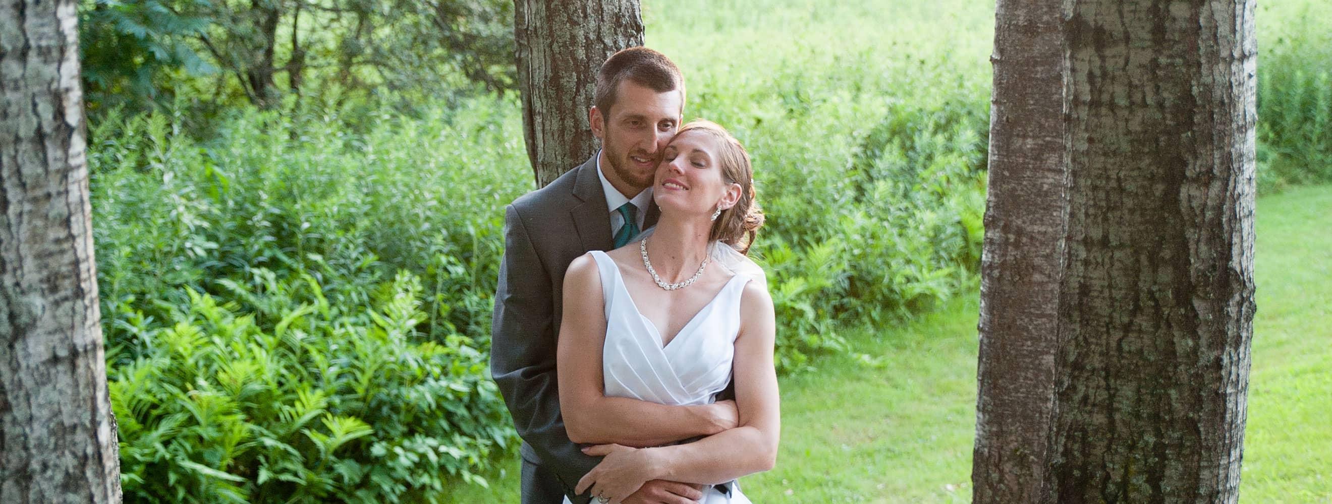 Newlyweds embrace among the trees
