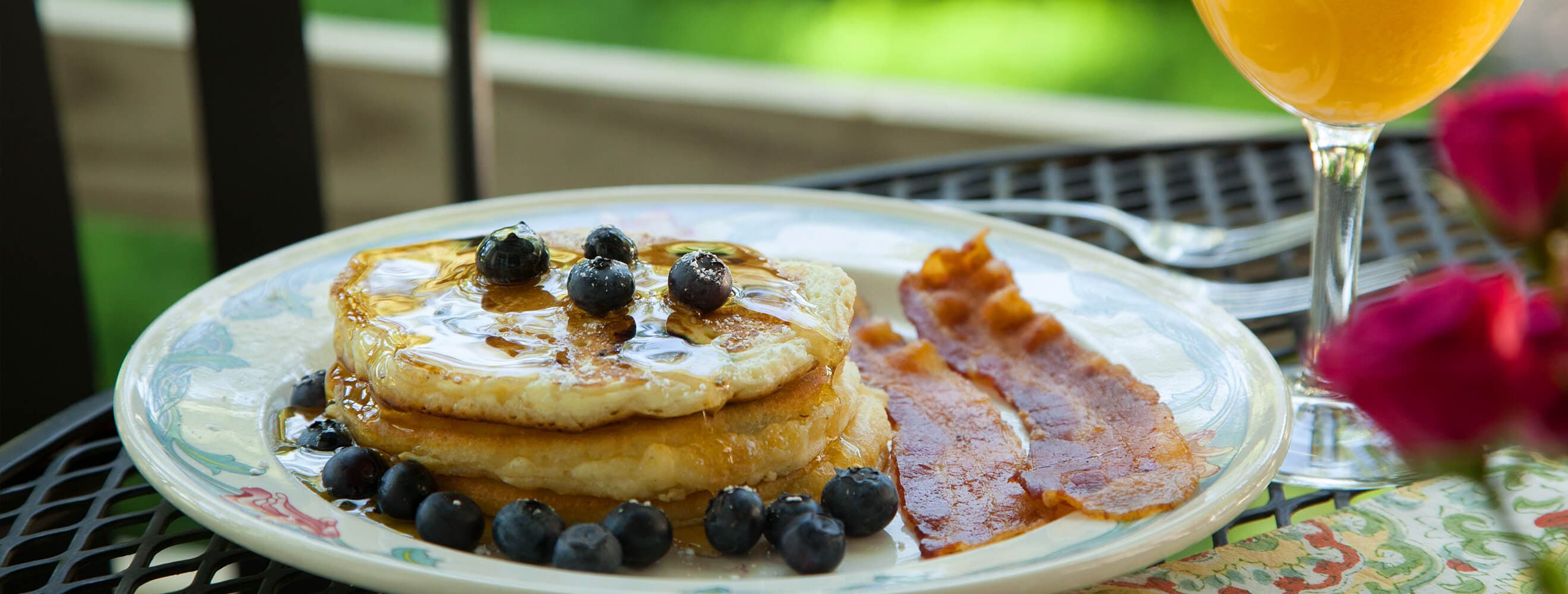blueberry pancakes with orange juice on outdoor dining table