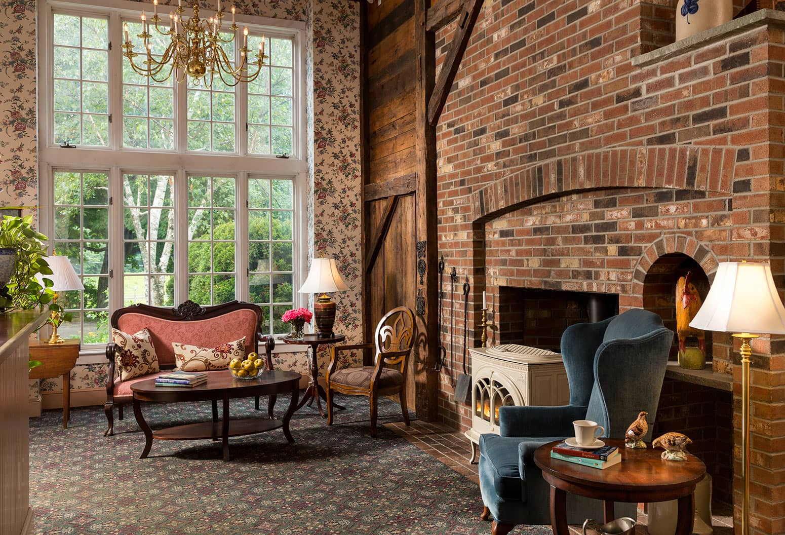 The Lobby of Chesterfield Inn with Exposed brick and white stove, loveseat, etc.