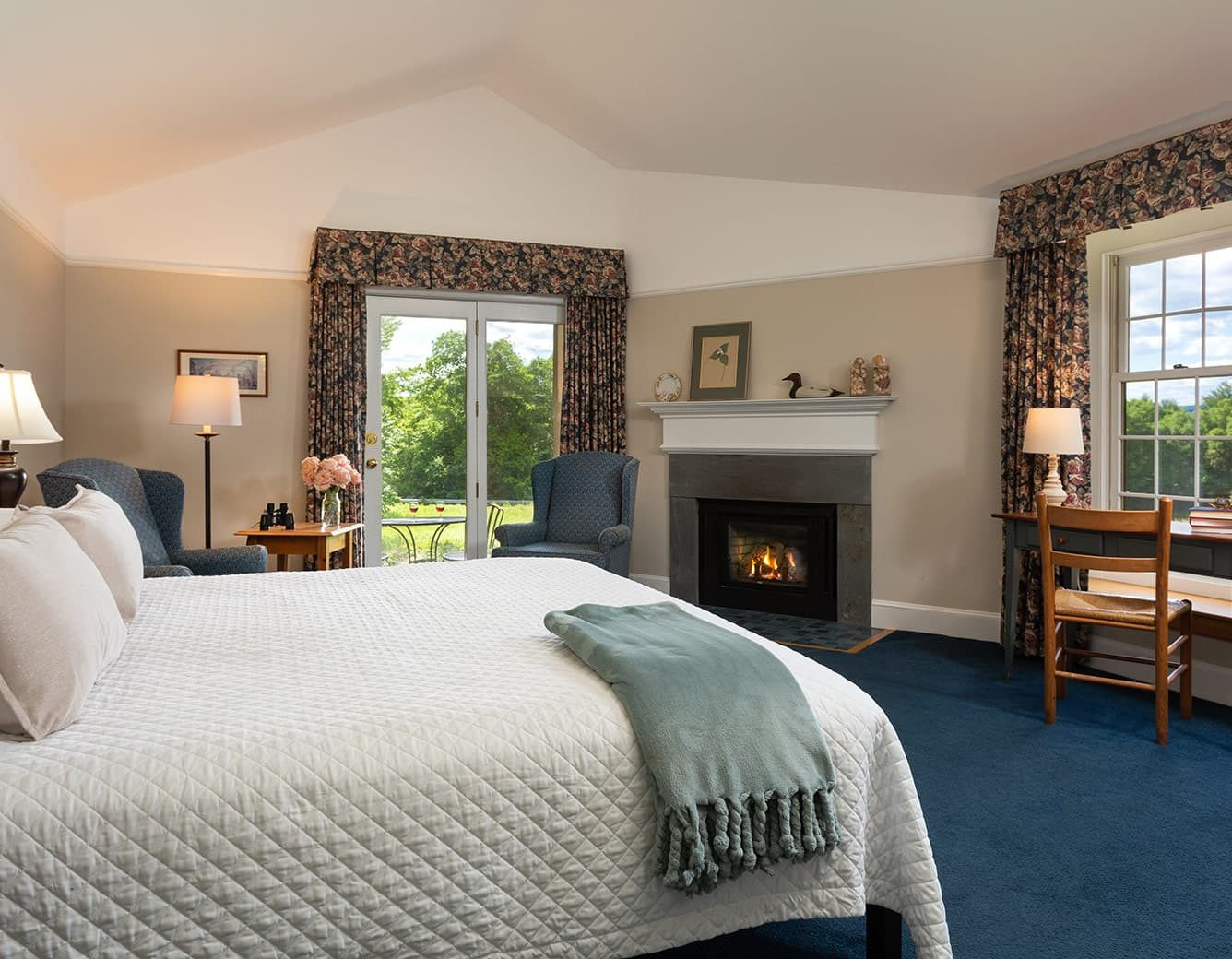 Bed, fireplace, desk and chairs in Room 22