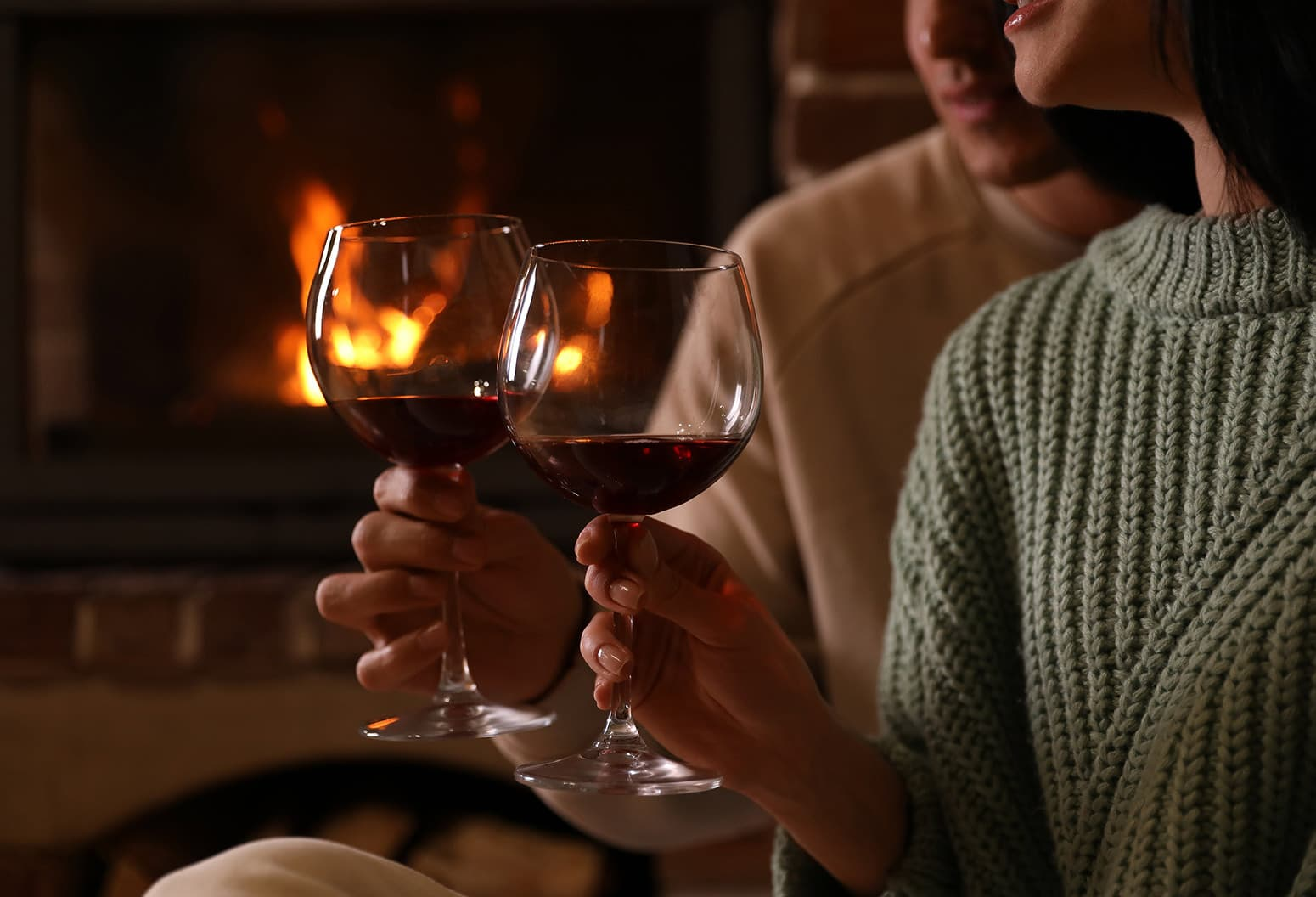 Couple with wine in front of a cozy fireplace