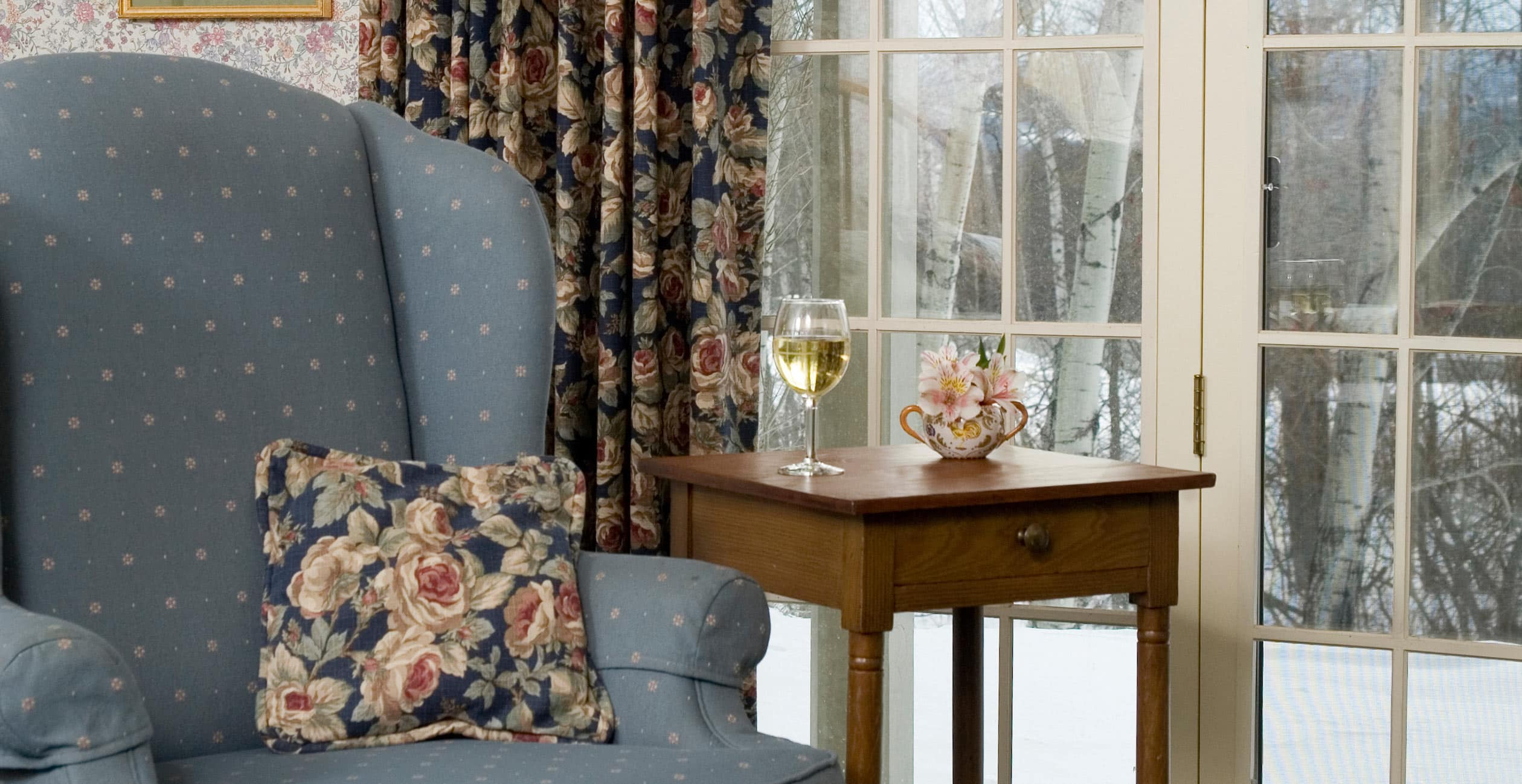 Comfortable chair with glass of white wine on table and snowy view
