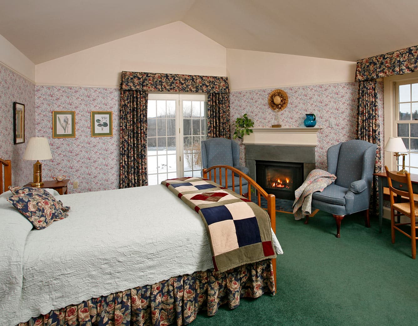 Bed, fireplace, two chairs in Room 22