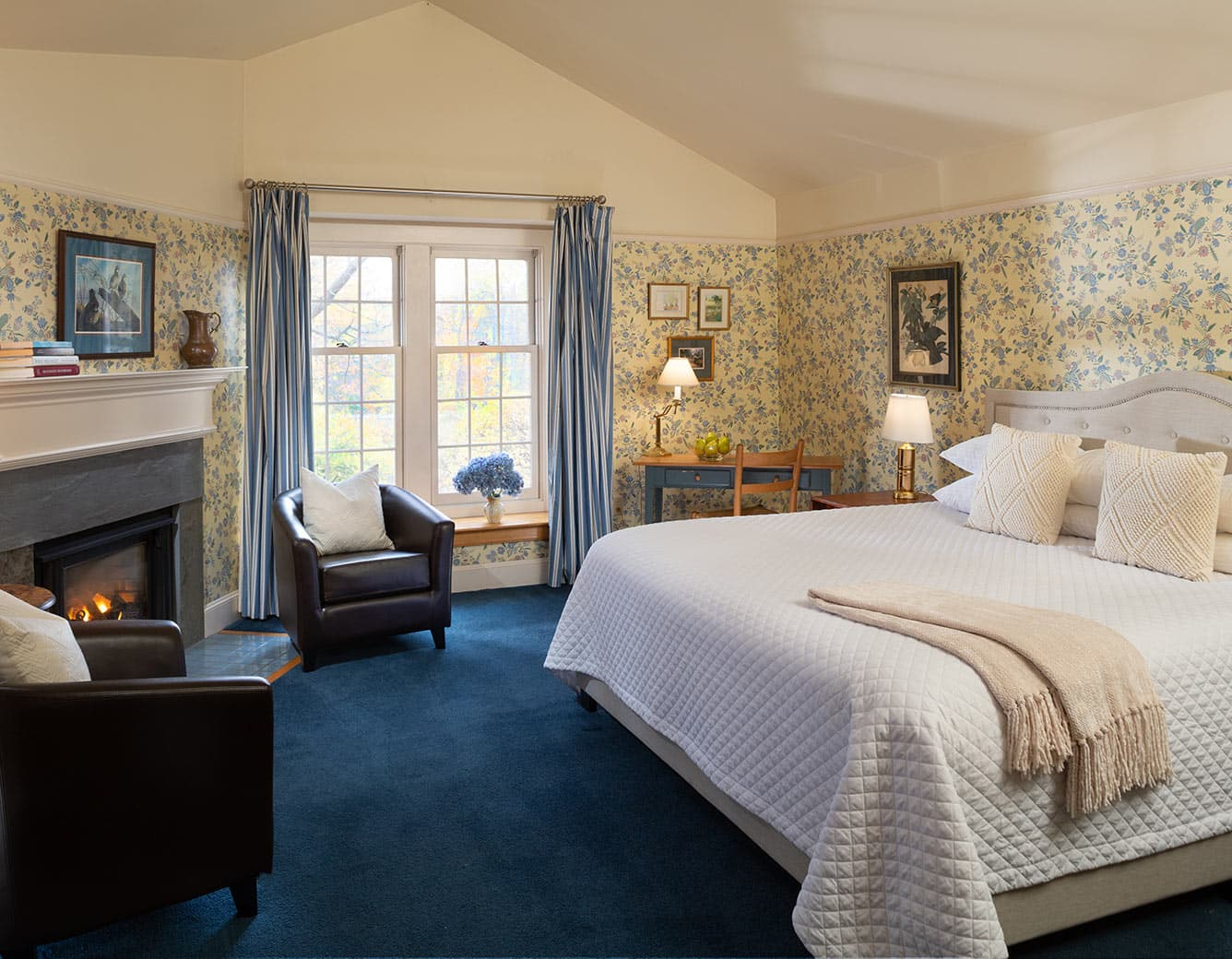 Bed, Fireplace, two leather chairs in Room 21