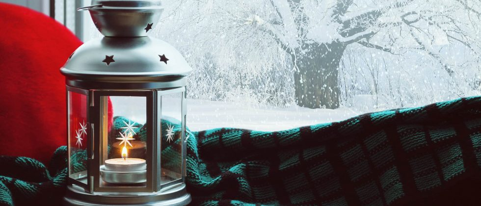 Holiday lantern in front of a snowy window