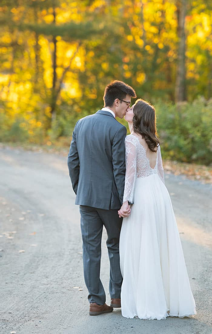 Bride and Groom share kiss outdoors in fall