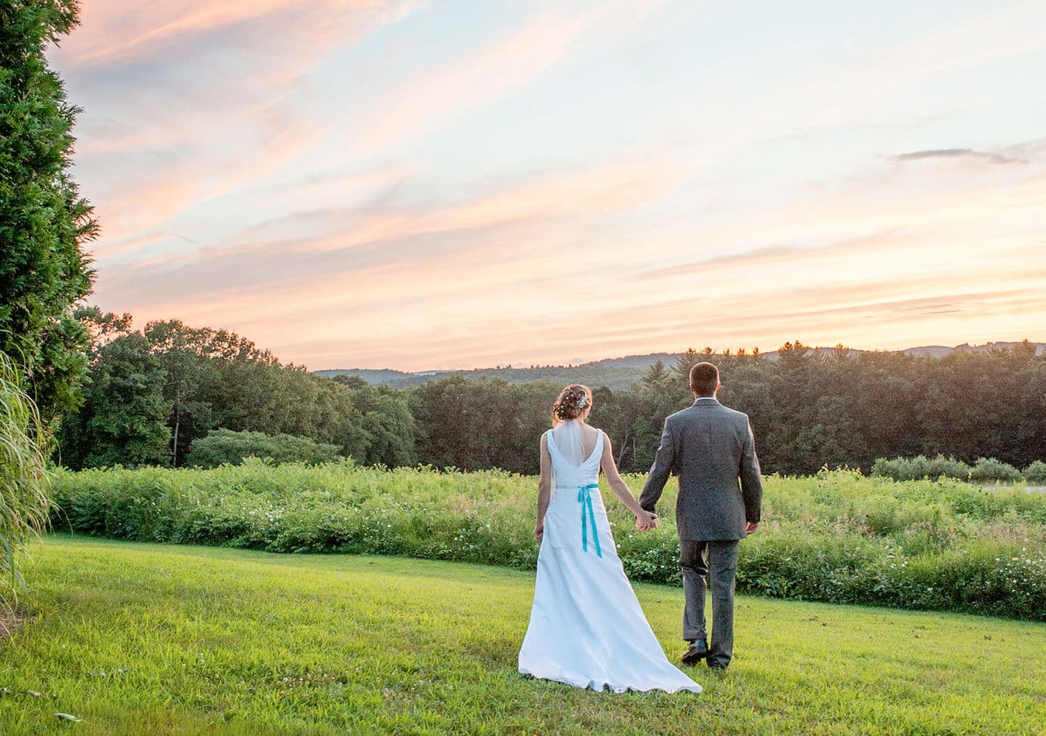 bride and groom in country with beautiful pink sky